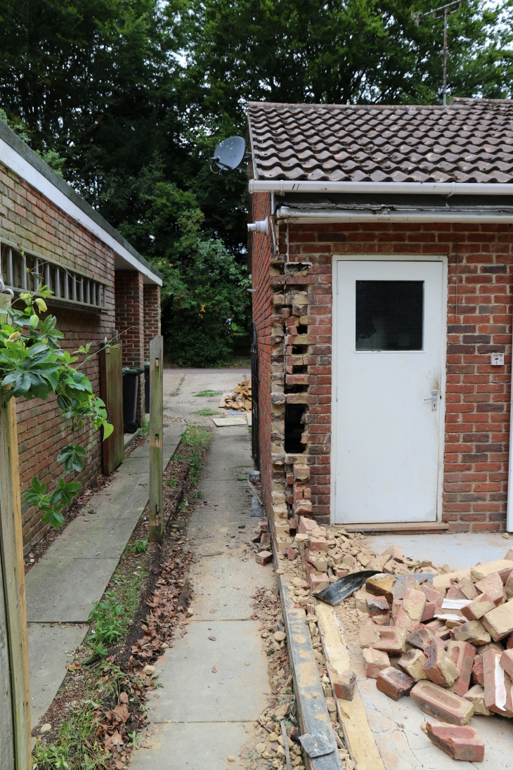 Conservatory - Neighbours fence removed. Large holes in garage wall.