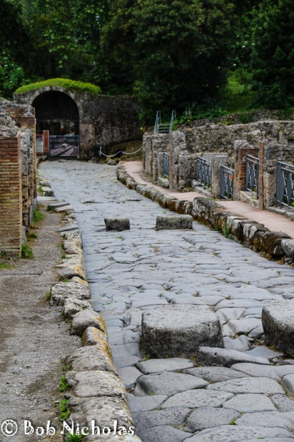 Pompeii - Street scene. Note the large blocks across the street. These are stepping stones, pedestrian crossings to enable the citizens of Popeii to avoid the detritus that would running down the road.