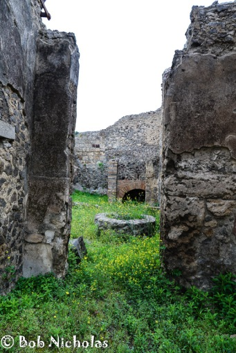 Pompeii - Bakery with flour grinder to the fore and the bread oven to the rear.